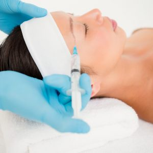 Kvinna får behandling med fillers i ansiktet